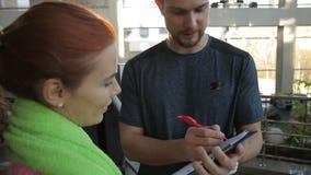 L'istruttore maschio sta scrivendo i risultati della donna nella palestra moderna video d archivio