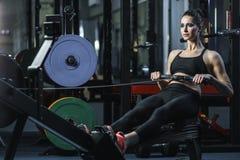 L'istruttore muscolare attraente di CrossFit della donna fa l'allenamento sul rematore dell'interno Fotografie Stock