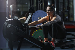 L'istruttore muscolare attraente di CrossFit della donna fa l'allenamento sul rematore dell'interno Immagini Stock Libere da Diritti