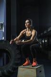 L'istruttore muscolare potente di CrossFit della donna salta durante l'allenamento alla palestra Immagini Stock