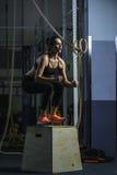 L'istruttore muscolare potente di CrossFit della donna salta durante l'allenamento alla palestra Immagine Stock