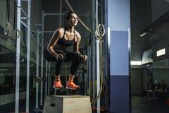 L'istruttore muscolare potente di CrossFit della donna salta durante l'allenamento alla palestra Fotografie Stock