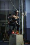 L'istruttore muscolare potente di CrossFit della donna salta durante l'allenamento alla palestra Fotografia Stock Libera da Diritti