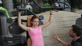 L'istruttore personale di forma fisica controlla corretto dell'esercizio su attrezzatura della donna stock footage