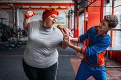 L'istruttore prende l'hot dog alla donna grassa, motivazione Fotografie Stock