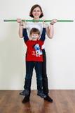 L'istruttore sta tenendo un bastone, ragazzino sta appendendo su, allungamento Fotografia Stock Libera da Diritti
