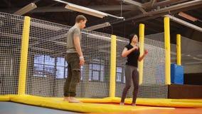 L'istruttore trampolining sta insegnando alla giovane donna a saltare in una palestra video d archivio