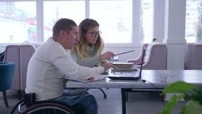 L'istruzione per handicappato, occhiali delle donne dell'istitutore tiene la lezione per gli uomini disabili sulla sedia a rotell video d archivio