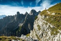 L'Italia, dolomia - equipaggi la viandante che sta molto lontano dal bordo delle rocce sterili Fotografie Stock