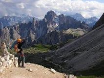 L'ITALIA, DOLOMIA, luglio 2011: Alpinista che sta sull'alta valle eccessiva del percorso e che prende una foto delle montagne Immagine Stock Libera da Diritti