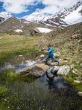L'Italia, Lombardia, alpi, bambino salta fra due rocce in un mounta Immagini Stock Libere da Diritti