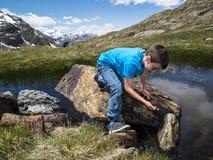 L'Italia, Lombardia, alpi, giochi da bambini vicino ad un lago dell'alta montagna Fotografia Stock Libera da Diritti
