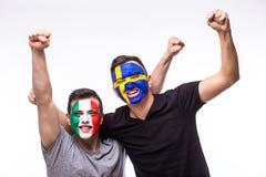 L'Italie contre la Suède sur le fond blanc Les passionés du football des équipes nationales célèbrent, dansent et crient Image stock