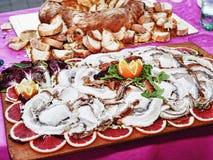 L'Italien traditionnel Porchetta s'est présenté avec les oranges et la salade rouges sur le plateau en bois photographie stock libre de droits