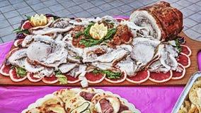 L'Italien traditionnel Porchetta s'est présenté avec les oranges et la salade rouges sur le plateau en bois photographie stock