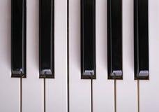 L'ivoire blanc et les clés noires d'un piano Photos stock
