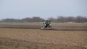 L'ivrogne et détachent le sol sur le champ avant l'ensemencement Le tracteur laboure un champ avec une charrue clips vidéos