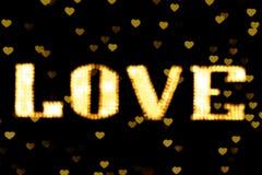 L'or jaune-clair au néon jaune brouillé du signe LED Bokeh d'AMOUR d'or des textes sur le bokeh de fond allume le coeur doucement Photos libres de droits