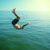 L'jeune homme sautant en mer photographie stock