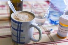 L?karbehandling under frukosten, kapslar bredvid ett exponeringsglas av vatten, begreppsm?ssig bild arkivbild