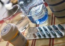 L?karbehandling under frukosten, kapslar bredvid ett exponeringsglas av vatten, begreppsm?ssig bild royaltyfria foton