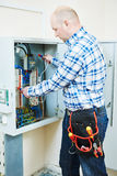 L'électricien travaille avec l'appareil de contrôle de mètre électrique dans la boîte de fusible Photographie stock libre de droits