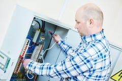 L'électricien travaille avec l'appareil de contrôle de mètre électrique dans la boîte de fusible Images stock