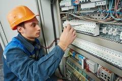 L'électricien travaille avec l'appareil de contrôle de mètre électrique dans la boîte de fusible Photo libre de droits