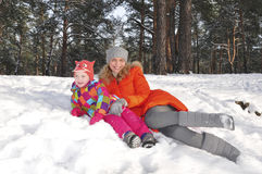 L little girl with her mother lying on the snow in the pine fore Stock Photography