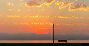 L?mpada de rua e banco na frente do por do sol vermelho brilhante bonito imagens de stock royalty free