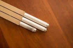L?mpadas fluorescentes na tabela, queimada e nova fotografia de stock