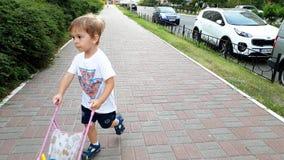 l?ngd i fot r?knat 4k av den f?rtjusande litet barnpojken som g?r p? gatan med leksaksittvagnen f?r docka Pojke som spelar med le arkivfilmer