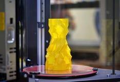 L'objet sous forme de vase jaune se tient sur l'imprimante du bureau 3d Images stock