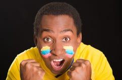 L'obscurité de Headshot a pelé le mâle utilisant la chemise jaune du football devant le fond noir, peinture faciale de drapeau, f Images stock
