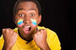 L'obscurité de Headshot a pelé le mâle utilisant la chemise jaune du football devant le fond noir, peinture faciale de drapeau, f Images libres de droits