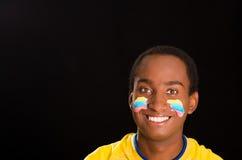 L'obscurité de Headshot a pelé le mâle utilisant la chemise jaune du football devant le fond noir, peinture faciale de drapeau, f Photo libre de droits