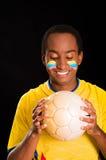 L'obscurité de Headshot a pelé le mâle utilisant la chemise jaune du football devant le fond noir, peinture faciale de drapeau, f Image libre de droits