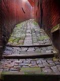 L'obscurité a pavé l'allée en cailloutis raide à Durham Angleterre avec les murs rouges Photo stock