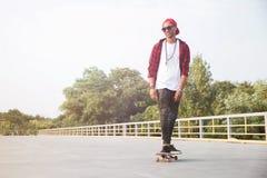 L'obscurité a pelé le skateboarding de port de lunettes de soleil et de chapeau d'homme Photos libres de droits