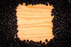 L'obscurité a rôti des grains de café sur le fond en bois de table Image stock