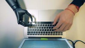 L'obtention de clavier numérique d'ordinateur portable a dactylographié dessus par un bras robotique de cyborg clips vidéos