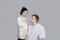L'occhio del paziente d'esame di medico con la torcia elettrica immagine stock