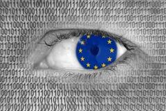 L'occhio della donna con la bandiera dei numeri dell'Unione Europea di E. - e di codice binario Fotografie Stock