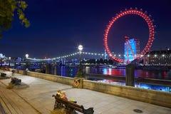 L'occhio di Londra, la ruota di ferris, illuminata ed il Tamigi si mette in bacino alla notte Fotografie Stock