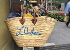 L`Occitane branded straw bag hanging on store door Stock Photo