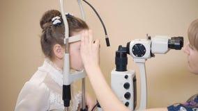 L'oculista della donna sta correggendo la testa della bambina vicino all'apparato biomicroscopy video d archivio