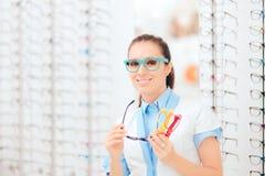 L'oculista Holding Many Eyeglasses incornicia in negozio ottico fotografia stock