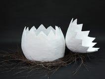 L'oeuf énorme de papier-pierre dans un nid des branches est découvert dans deux parts sur un fond noir Photos stock