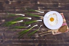 L'oeuf au plat, la ciboulette verte, le plat blanc, le couteau et la fourchette ressemblent à la concurrence de sperme Spermatozo Images stock