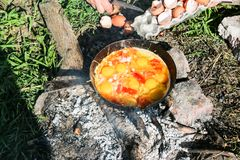 L'oeuf brouillé a fait frire sur des charbons dans la casserole sur le feu ouvert, cuisinier au-dessus d'un feu ouvert Image stock